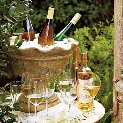 Um recipiente em pedra abriga várias garrafas de vinho branco mergulhadas em gelo. Ele está sobre uma mesa ao ar livre e ao lado se vêem várias taças de cristal