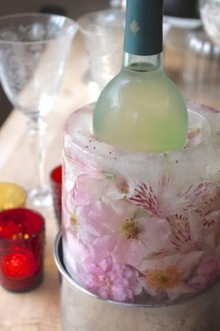 Em primeiro plano vemos uma garrafa de vinho branco envolvida com um cilindro de gelo através do qual se vêem rosas e flores prensadas .