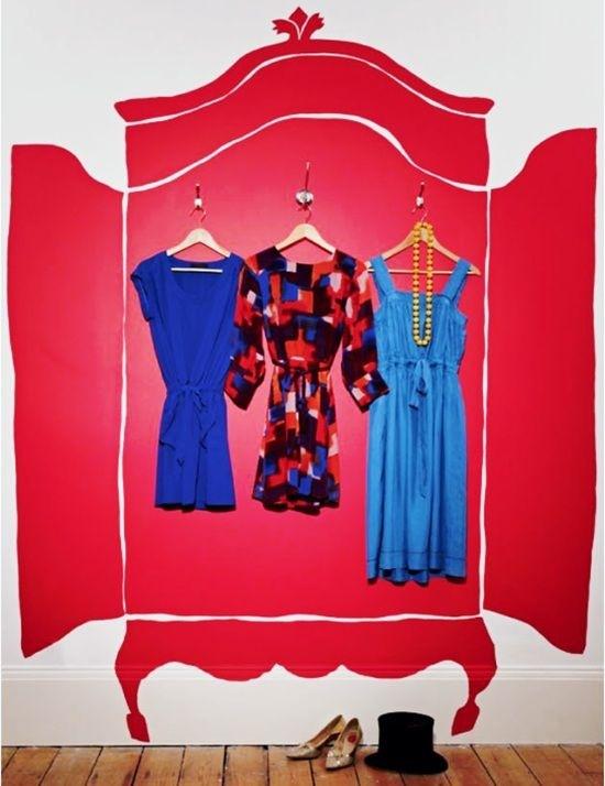 Um desenho de um guarda roupa vermelho está pintado sobre uma parede branca. Ele tem as portas curvas abertas em do que seria o seu interior estão pendurados 3 vestidos em cabides que, na verdade , estão pendurados em ganchos na parede. É um truque de ilusão de ótica.
