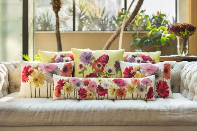Sobre um sofá de cor creme colocado em frente a uma janela , estão colocadas várias almofadas de fundo também creme porém estampadas com enormes flores de todas as cores. O efeito é de alegria e muita cor.