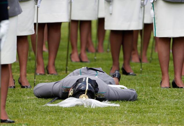 Em cerimônia oficial, tropa de militares perfilados estão num galpão. A frente um comandante e atrás um militar desmaiado de cara no chão.