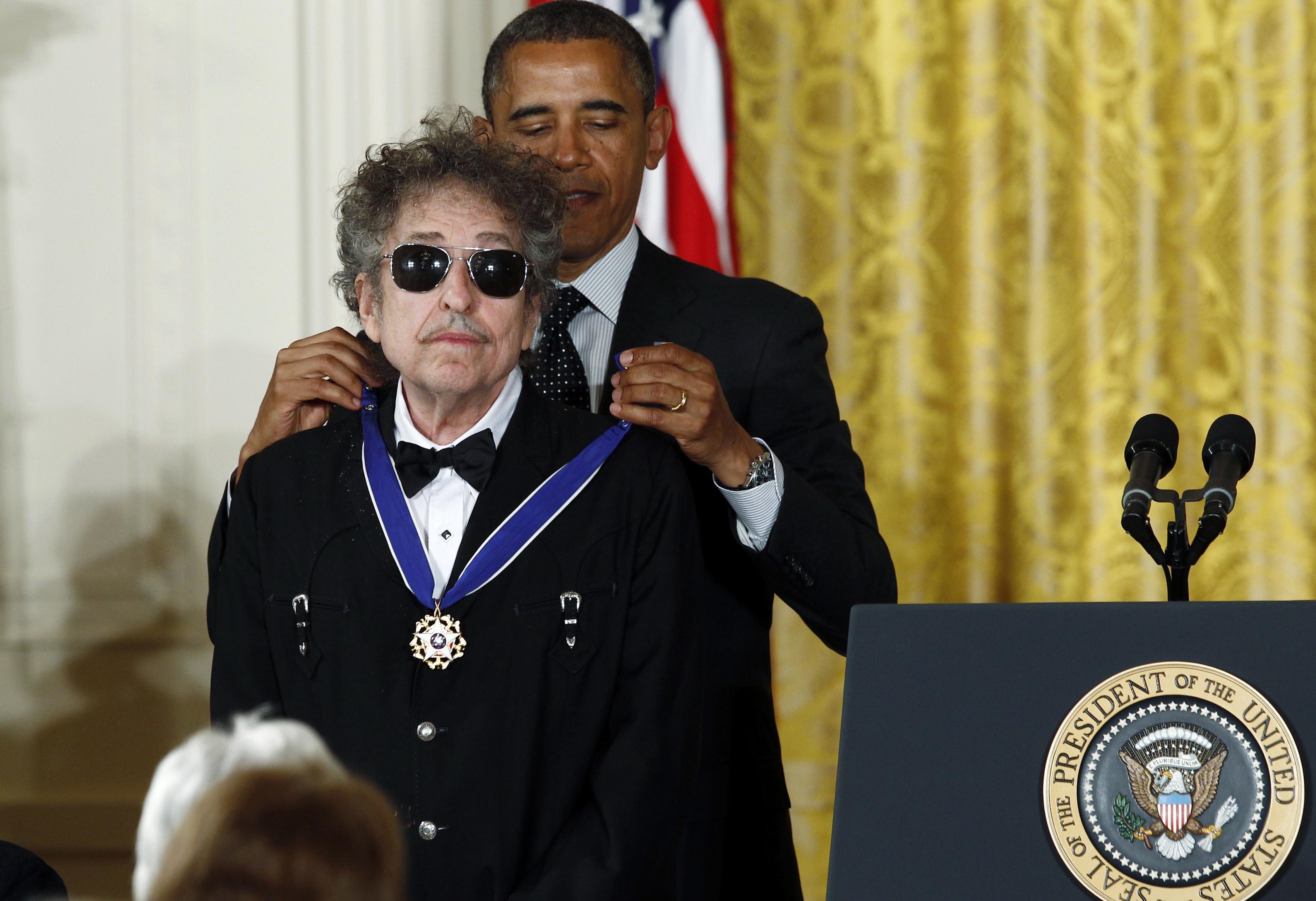 Presidente Barack Obama , outorga uma medalha do cantor Bob Dylan. Estão no Salão Nobre da Casa Branca, os dois estão em pé, Presidente logo atrás do cantor e fecha o colar da medalha. Bob Dylan usa óculos escuros e bigode, está de roupa escura, camisa branca e gravata borboleta preta. Presidente Obama, usa terno , camisa branca e gravata escura com detalhes pontuais de cor clara.