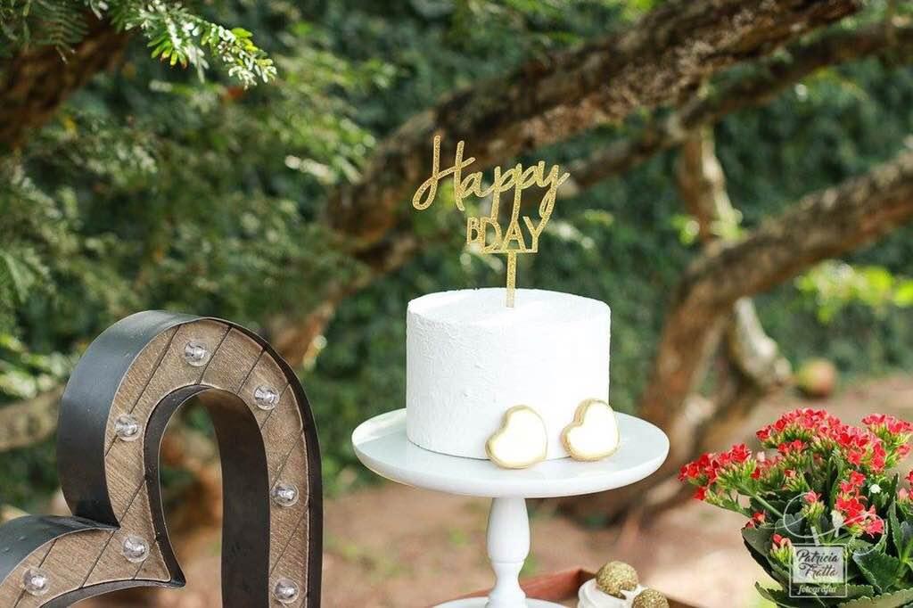 Uma mesa pequena e redonda apoia um prato de bolo branco com um cactus de açúcar verde confeitado enfeitando. Ao redor pequenos vasos de cactos naturais compõem o visual.