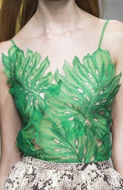 a foto mostra uma regata de renda verde onde a renda faz o desenho de grandes filhas de vegetação em tom verde claro.