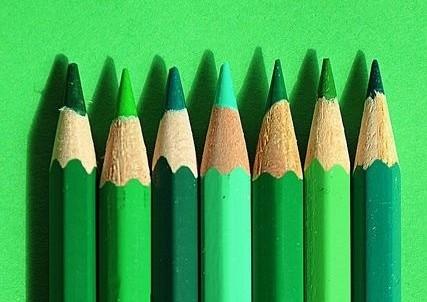 sete lápis em diferentes tons de verde estão enfileirados e apontados com suas pontas para cima sobre um fundo verde claro bem forte