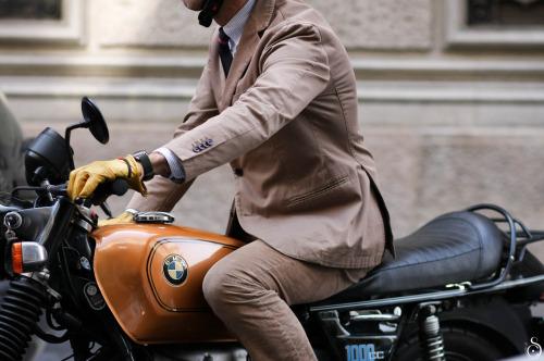 Uma moto BMW cim capô em madeira ou fibra imitando a cor de madeira acobardar. Sobre ela um usuário de terno esportivo em algodão cor de tabaco e gravata escura dirige com as mãos enluvadas no guidão. Não aparece o rosto.