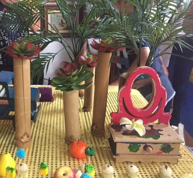 Mesa decorada para festa infantil, com vários objetos (frutas e folhas verdes) compõem o cenário.