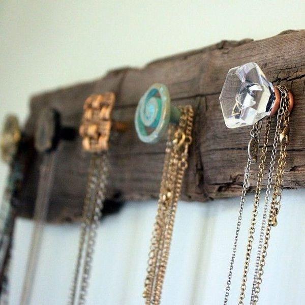 uma tábua rústica está pendurada na parede e nela, vários puxadores coloridos estão servindo de ganchos para colares e correntes de bijuteria