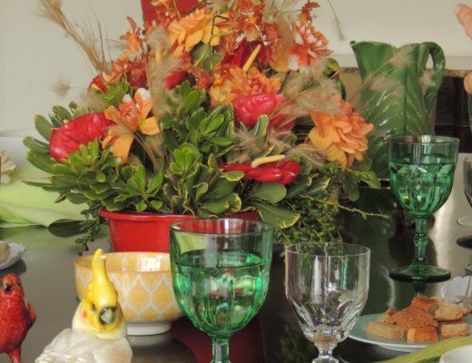 Mesa de jantar montada , com todos os utensilios e acessórios. Flores ao centro na cor branca e laranja. Algumas taças estão em detalhe - a taça de água em tom verde e a taça de vinho branco, em cristal transparente. Como decoração muitos pássaros, araras, papagaios em porcelanas estão em volta do vaso de flores