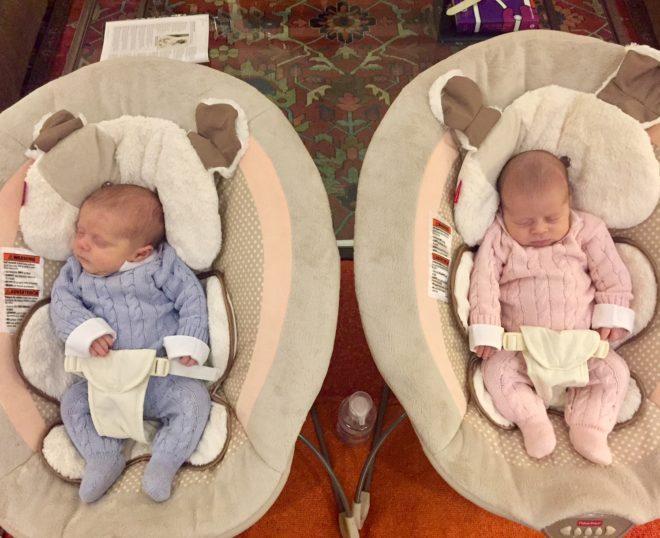 dois bebês com cerca de um mês estão em duas cestas diferentes um vestido de azul outro de cor de rosa e ambos dormem .