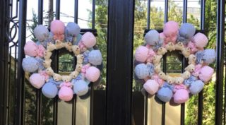 duas guirlandas feitas de cursinhos de pano rosa e azul estão penduradas em um portão de grades de ferro pretas em um claro sinal de boas vindas a quem chegar e sinalizando que nessa casa nasceram bebês.