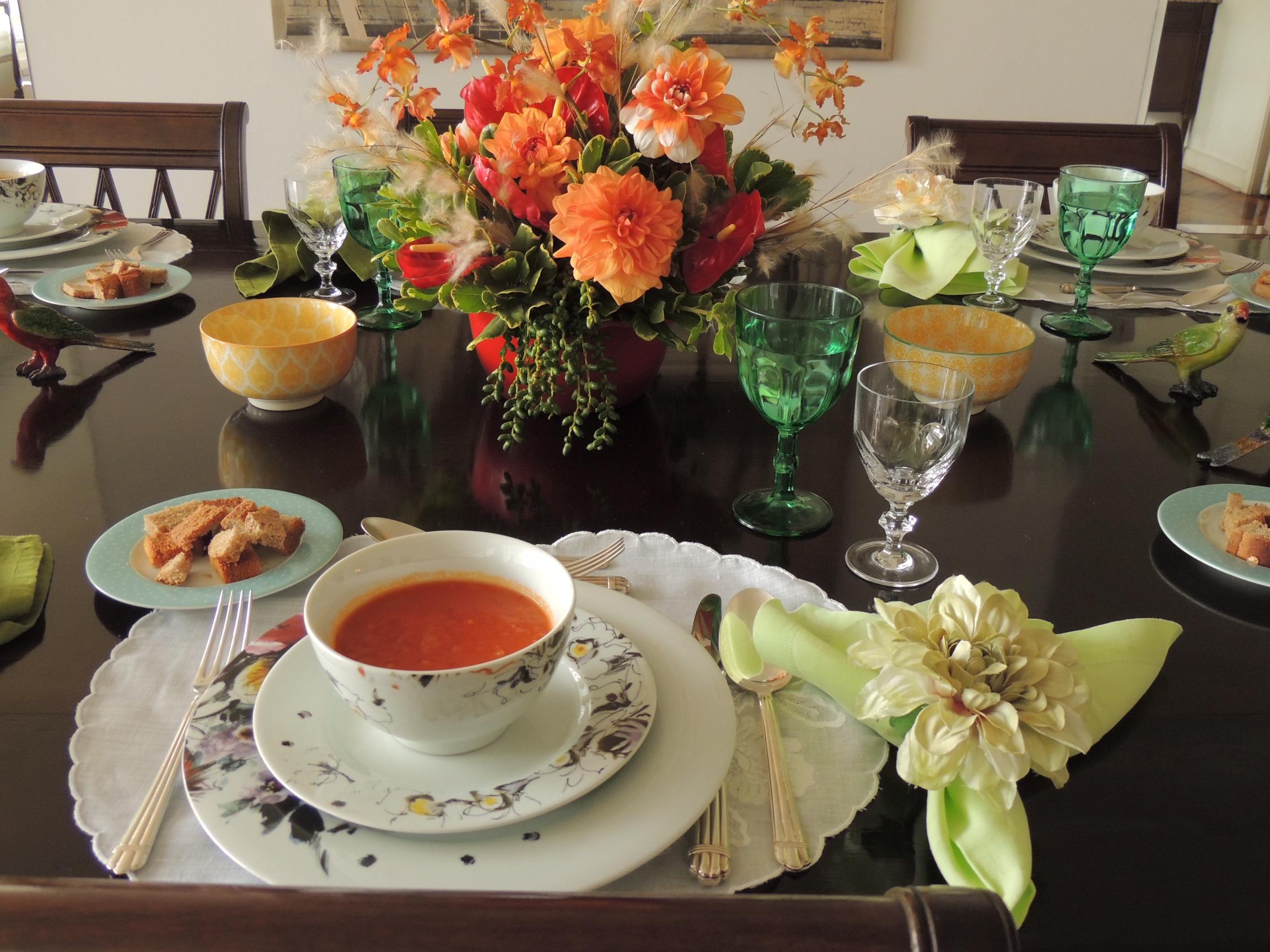 Mesa de jantar montada , com todos os utensilios e acessórios. Flores ao centro na cor branca e laranja. Algumas taças estão em detalhe - a taça de água em tom verde e a taça de vinho branco, em cristal transparente.