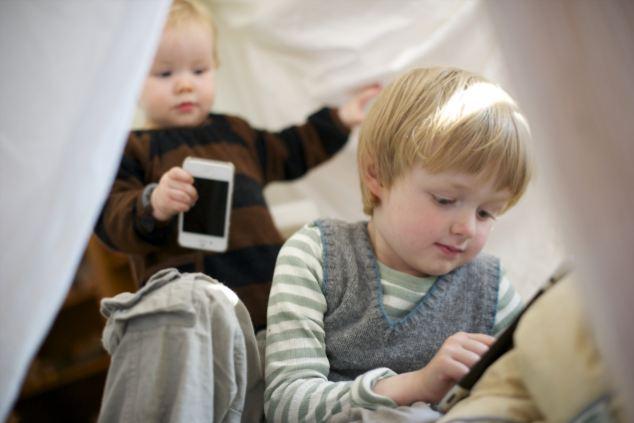 duas crianças uma mais velha do que a outra (5 anos) e (1 anos), que estão brincando um smartphones e tablets.