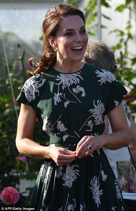 Kate Middleton, em visita a Chelsea Flowers Show, sorri para todos, usando um vestido verde escuro e com detalhes de flores na cor branca, tem seus cabelos presos, Ea está andando , olhando a exposição.