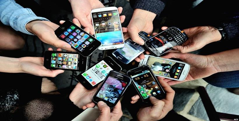 Inúmeros braços, estendidos num círculo, todos segurando nas mãos smartphones, celulares, .