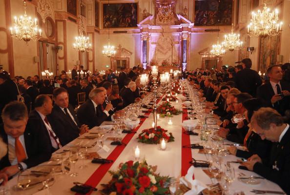Banquete Oficial com uma mesa retangular enorme com 50 pessoas de cada lado, a maioria homens de terno, e ao centro da mesa temos muitas pequenas velas acesas. e alguns candelabros maiores com velas acesas e com as bases floridas.