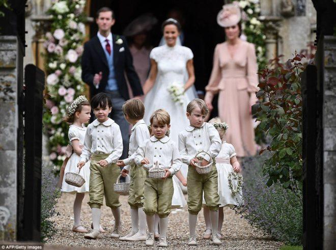Casal Pippa Middleton e James Matthews, após o seu casamento, saem da igreja, ladeados pela Kate Middleton , usando um longo nude e um chapéu da mesma cor, a sua frente os pajens e daminhas, Um deles seu filho.