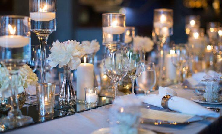 Mesa de jantar com muitos objetos de decoração, tudo em tons claros, alguns em branco. muitas velas na base ao centro e outras velas em castiçal em vidro com água .
