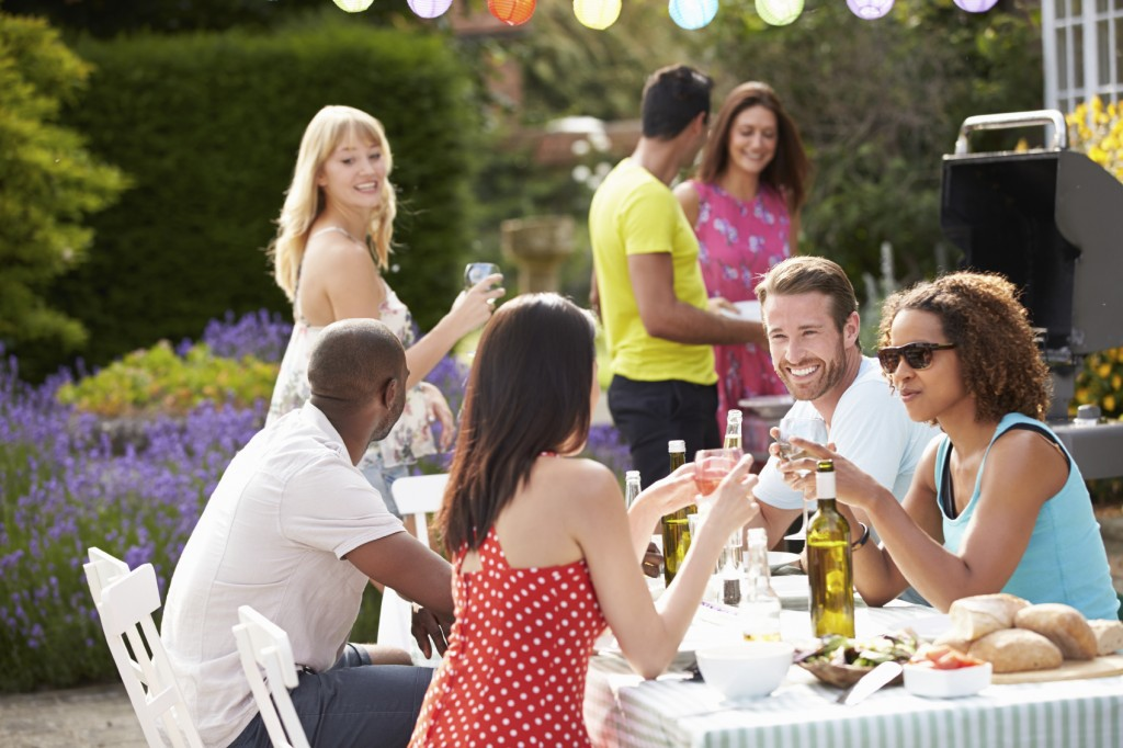 Num jardim, pessoas participam de um almoço. Á mesa dois casais brindam com taças de vinho , enquanto outras pessoas estão em pé junto a outra mesa.